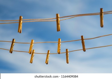 Wooden clothespins on a clothesline against a blue sky background
