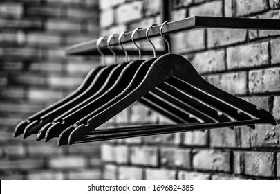 Wooden coat hanger clothes. Fashionable different types of hanger. Many wooden black hangers on a rod. Store concept, sale, design, empty hangers. Black and white.