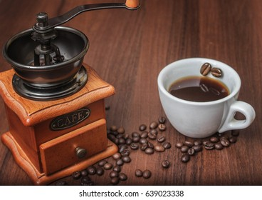 A wooden coffee grinder next to a cup of coffee on a tree with coffee beans