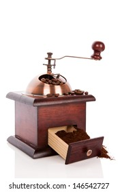 Wooden coffee grinder with open drawer with ground coffee isolated on white background with reflection. Luxurious coffee break.