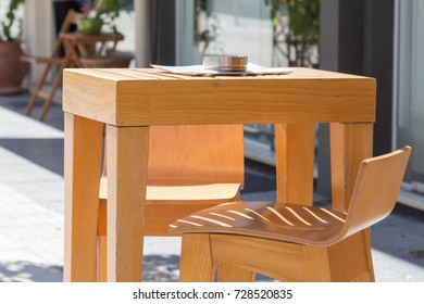 wooden coffee table with ashtray and stool on a terrace in a sunny day