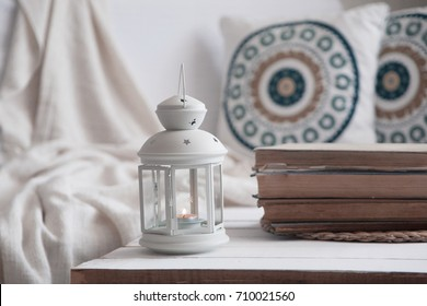 Wooden coffee table with lantern and cozy sofa with pillows. Living room interior and home decor concept. Toned image