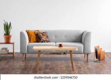 Wooden coffee table in the middle of elegant living room with grey couch and magazine rack on the wooden floor, real photo
