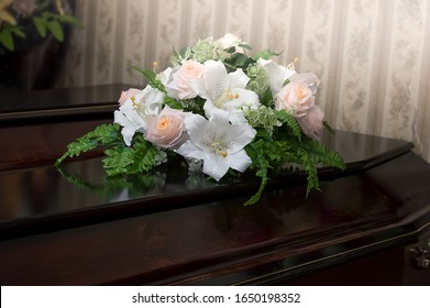 A wooden coffin of dark color is decorated with flowers. Funeral, burial. Death.