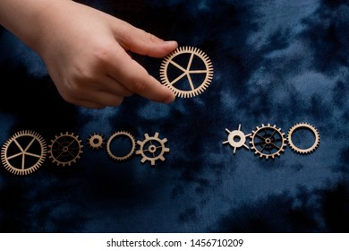 Wooden cogwheels on a fabric industry concept information.