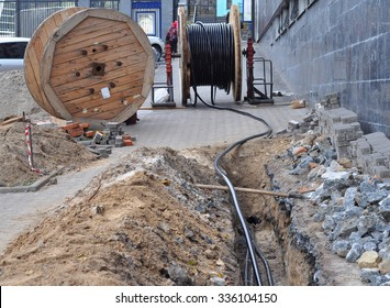 Wooden coil of electric cable  and optical fibres in the digging on the street construction site