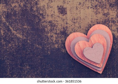 Wooden colorful hearts inside of each other on shabby chic surface