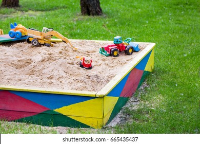 Wooden colorful sandbox with with toys in a garden.