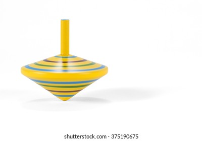 Wooden and colorful spinning top, turning on white desk.
