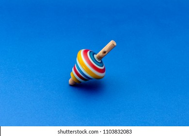 Wooden colorful spinning top 'whirligig' on the blue background.
