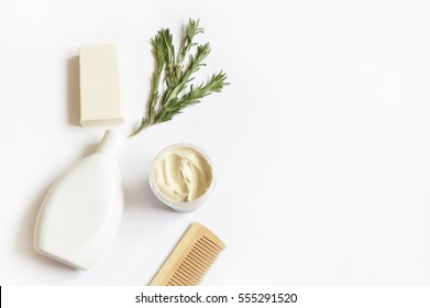 Wooden comb, rosemary, shampoo bottle, baby soap, mask of cosmetic white kaolin and toy horse. Natural organic bath products. Flat lay photo, top view. Photography for design site and beauty blog