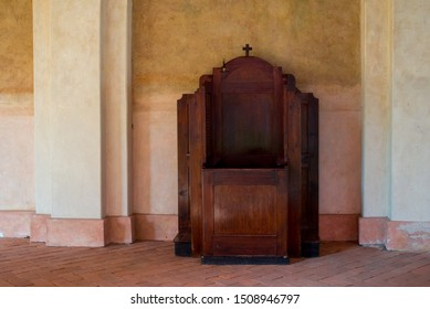 Wooden confessional in the cloister in the old church in the sunlights. Empty wooden old confessional.