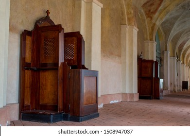 Wooden confessionals in the cloister in the old church in the sunlights. Empty wooden old confessional.