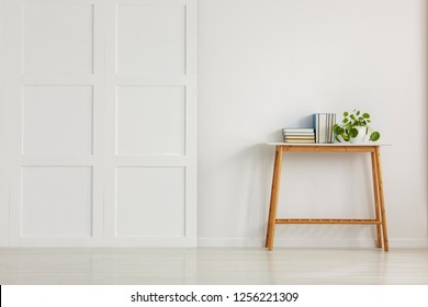 Wooden console table with books and plant in pot on empty white wall
