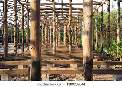 Wooden construction frame with logs and timber from an old deconstructed rice mill warehouse in Thailand.