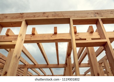 Wooden construction of an unfinished house. Skeleton of a building made of beams.