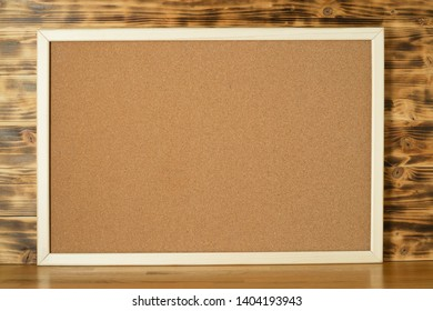 Wooden corkboard frame on wood table and background.