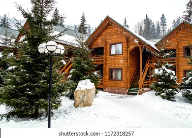 Wooden cottage house in mountain resort. Christmas winter landscape. Beautiful winter cottage covered snow