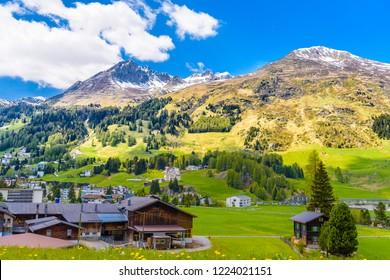Wooden cottage houses on green fields, Davos,  Graubuenden, Switzerland