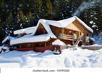 Wooden cottage near the pine forest, covered in snow