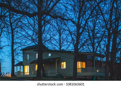 wooden cottage new river at night time with light in window, blue sky.