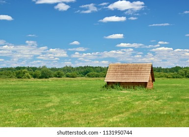 a wooden cottage on a meadow under a blue sky with clouds and a forest in the background