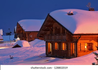 Wooden cottage in the winter's evening.