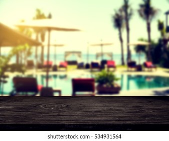 Wooden counter top background, with blurred defocus tropical resort in sunrise, vintage tone