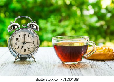 A wooden countertop on a blur of fresh green abstract background. Clock on the table in the green garden at 6 o'clock, bakery, cake, black tea, breakfast in the open air