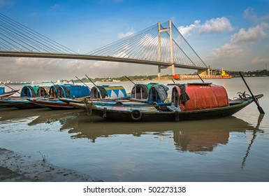 Wooden country boats on river Hooghly with Vidyasagar bridge at the backdrop. These boats are used for pleasure trips on the river adding a flavor of heritage to the banks..