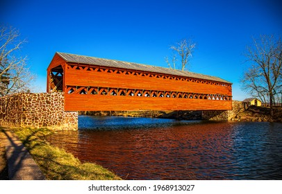 Wooden covered bridge over the river. Red wooden covered bridge. Covered bridge over river