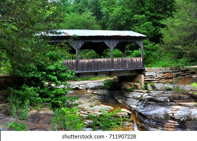Wooden covered bridge spans small creek in the Ozark Mountains of Arkansas.  Pool bubbles over rocky ledges.
