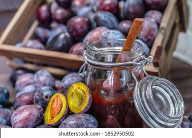 Wooden crate with plums and plum jam on a wooden table.