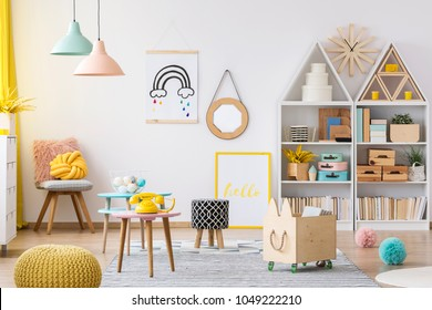 Wooden crate and yellow pouf in colorful kid's playroom interior with poster and patterned stool