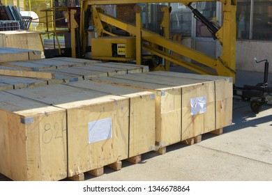 Wooden crates from China. There are five crates and there is a Telehandler hydraulic lift trailer behind. A hydraulic lift is a type of machine that uses a hydraulic apparatus to lift or move objects.