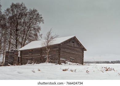Wooden crates have been piled by and old barn house in the rural Finland. The snow has covered the barn and the crates.