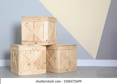 Wooden crates on floor at color wall. Space for text