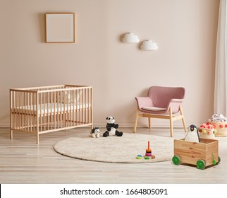 Wooden crib and bed for baby room, pink chair, carpet and frame on the wall.