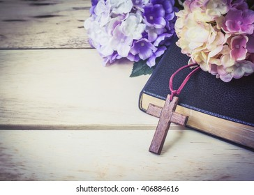 The wooden cross and black bible with flowers on wooden background
