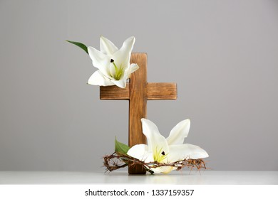 Wooden cross, crown of thorns and blossom lilies on table against color background