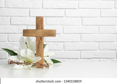 Wooden cross, crown of thorns and blossom lilies on table against brick wall, space for text