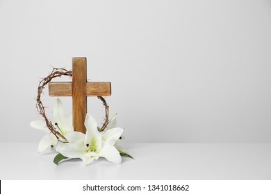 Wooden cross, crown of thorns and blossom lilies on table against light background, space for text