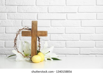 Wooden cross, crown of thorns, Easter eggs and blossom lilies on table against brick wall, space for text