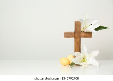 Wooden cross, Easter eggs and blossom lilies on table against light background, space for text