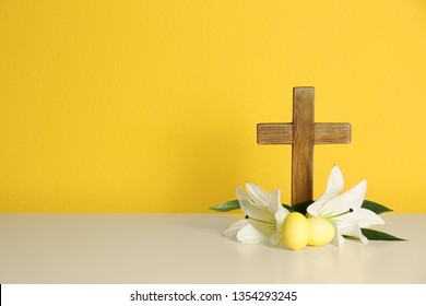 Wooden cross, Easter eggs and blossom lilies on table against color background, space for text