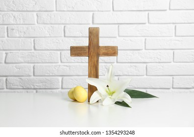 Wooden cross, Easter eggs and blossom lily on table against brick wall
