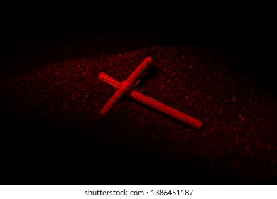 A wooden cross lies on the black ground. Prayer cross, amulet. Tied in the center with a red thread. Red light.