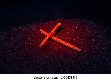 A wooden cross lies on the black ground. Prayer cross, amulet. Tied in the center with a red thread. Red and blue light.