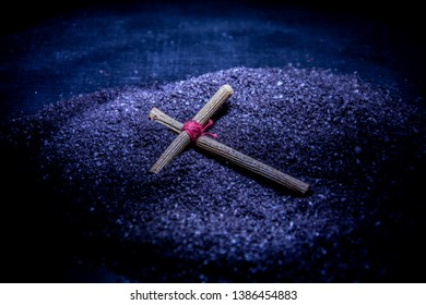 A wooden cross lies on the black ground. Prayer cross, amulet. Tied in the center with a red thread. Blue light.
