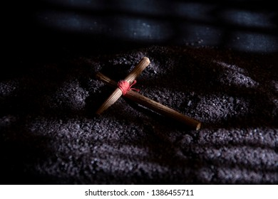 A wooden cross lies on the black ground. Prayer cross, amulet. Tied in the center with a red thread.